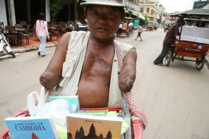 Southeast Asia, Cambodian mine victim selling books to tourists in Siem Reap near Angkor Temples. Photo: Anthony Maw.