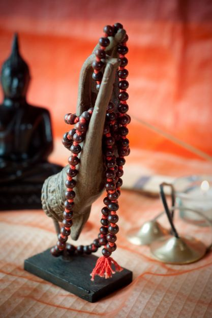 Travel souvenirs. Buddha hand from Cambodia with Japa Mala from India.