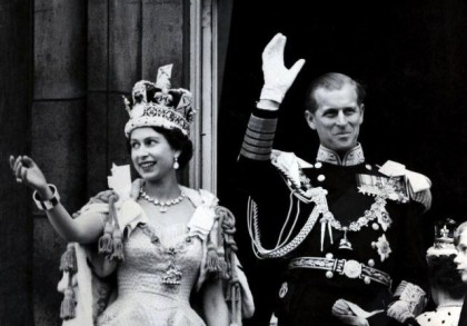 The Diamond Jubilee. Queen Elizabeth II wearing the Imperial State Crown and The Duke of Edinburgh in uniform of Admiral of the Fleet waving from the balcony to the onlooking crowds around the gates of Buckingham Palace after the Queen's Coronation on 2 June 1953. Photo: 2012queensdiamondjubilee.com